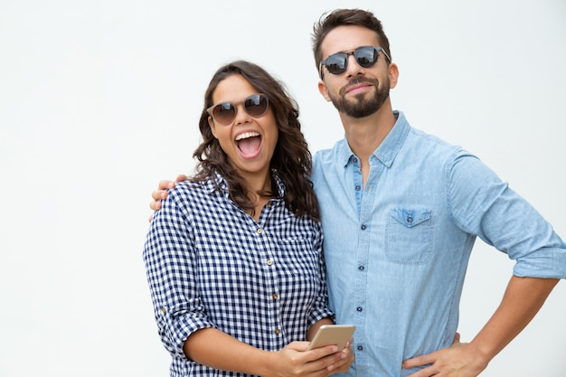 Coppie allegre in occhiali da sole facendo uso dello smartphone