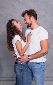 Coppie allegre nell'abbracciare bianco