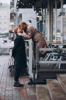 Coppie amorose adulte che baciano su una via
