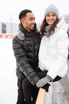 Coppie amorose attraenti che abbracciano e che pattinano alla pista di pattinaggio sul ghiaccio