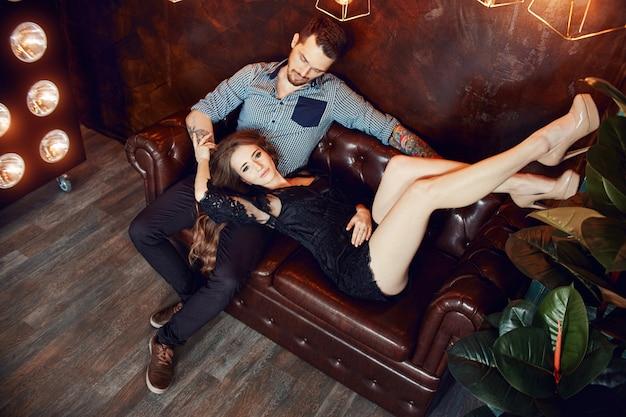 Coppie amorose che abbracciano sul divano contro le luci intense delle lampade. passione e tenerezza, uomo e donna si amano. donna che abbraccia un uomo