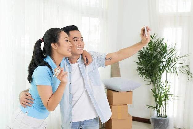 Coppie amorose che prendono selfie nella nuova casa