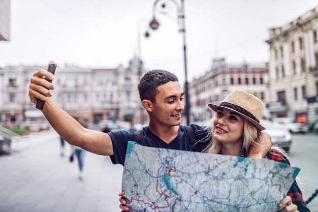Coppie amorose che prendono selfie sulla strada durante il viaggio