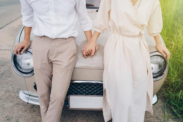 Coppie amorose che si tengono per mano sul viaggio stradale al tramonto.