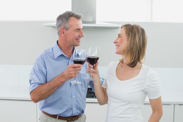 Coppie amorose che tostano i vetri di vino in cucina