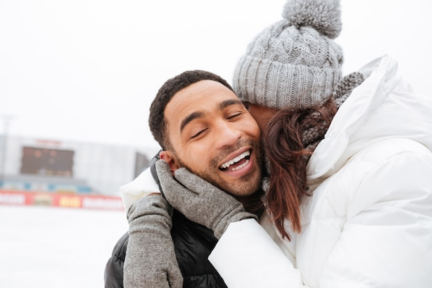 Coppie amorose di risata che abbracciano e che pattinano alla pista di pattinaggio sul ghiaccio