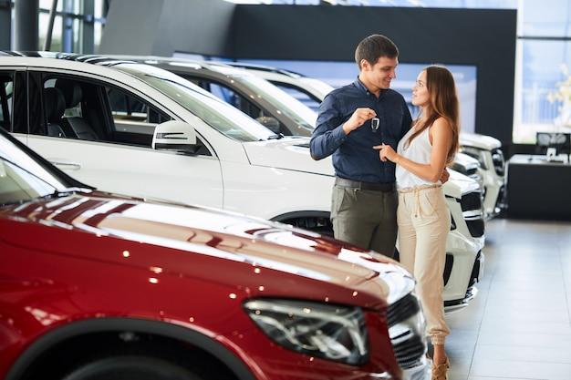 Coppie amorose felici che abbracciano vicino alla loro nuova automobile di lusso alla concessionaria.