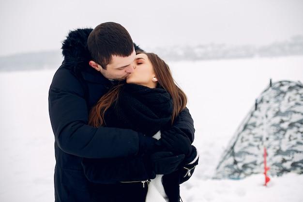 Coppie amorose in un clother di inverno che sta sul ghiaccio