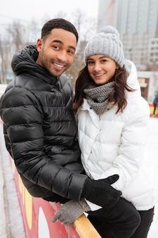 Coppie amorose sorridenti dei giovani che pattinano alla pista di pattinaggio sul ghiaccio all'aperto.