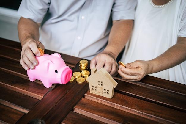 Coppie anziane che parlano della finanza con il porcellino salvadanaio