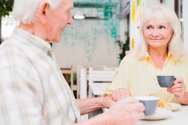 Coppie anziane contente che bevono tè e tenersi per mano