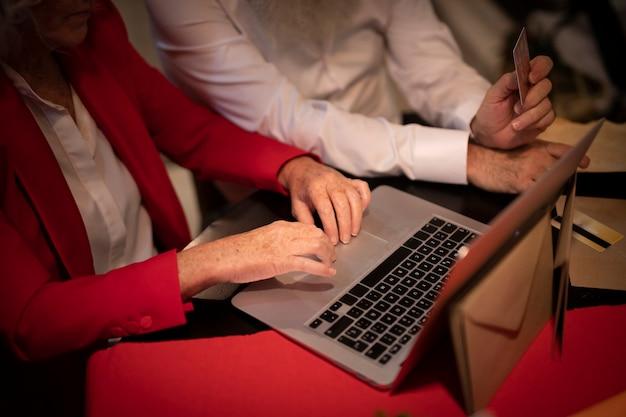 Coppie anziane del primo piano che per mezzo di un computer portatile