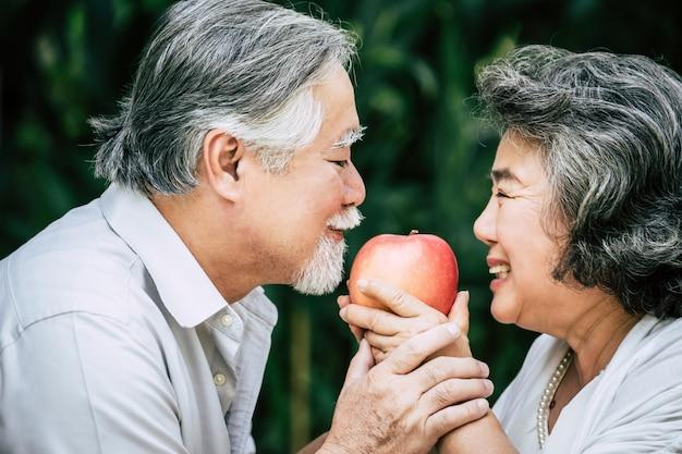 Coppie anziane giocando e mangiando un po 'di frutta