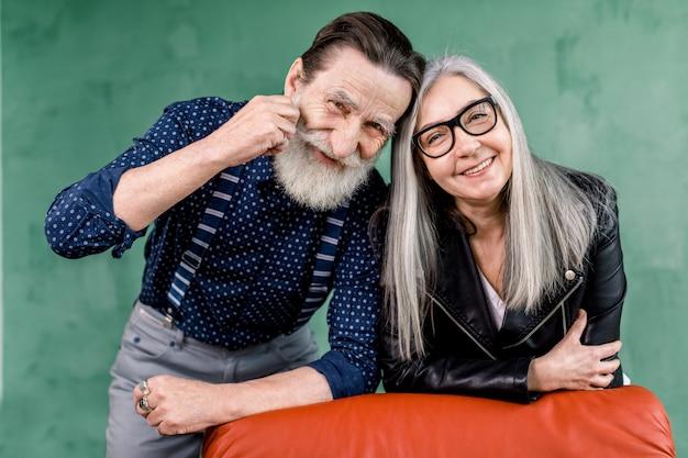 Coppie anziane piacevoli allegre che sorridono mentre essendo di ottimo umore, appoggiandosi sulla sedia molle rossa e toccando le fronti