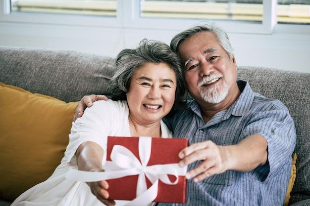 Coppie anziane sorpresa e confezione regalo in salotto