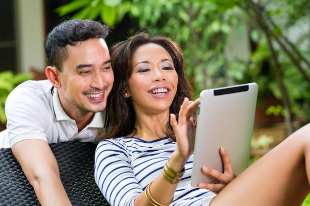 Coppie asiatiche all'aperto con un tablet pc