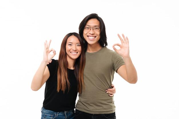 Coppie asiatiche allegre che mostrano gesto giusto mentre abbracciano, esaminando macchina fotografica