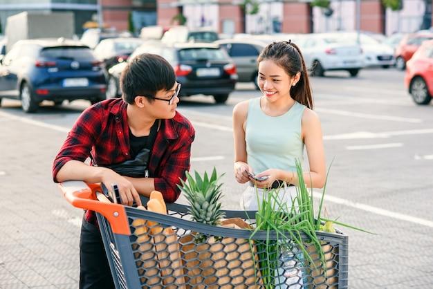 Coppie asiatiche che controllano il loro carrello in pieno di alimento biologico sano sui precedenti di grande deposito. concetto di cibo sano.
