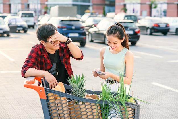 Coppie asiatiche che controllano il loro carrello in pieno di alimento biologico sano sui precedenti di grande deposito. il giovane vietnamita tiene la testa con la mano quando la sua ragazza conta i soldi per lo shopping.