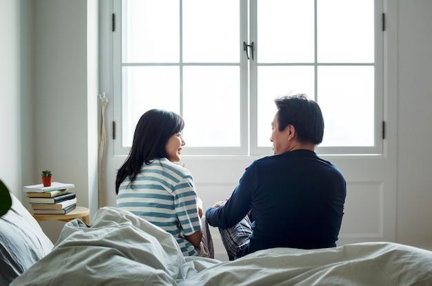 Coppie asiatiche che parlano insieme a letto