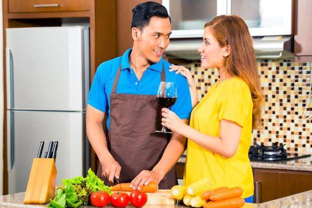 Coppie asiatiche che preparano alimento in cucina domestica