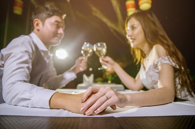 Coppie asiatiche che si tengono per mano insieme e bicchieri di vino incoraggianti. focus a portata di mano e anello.