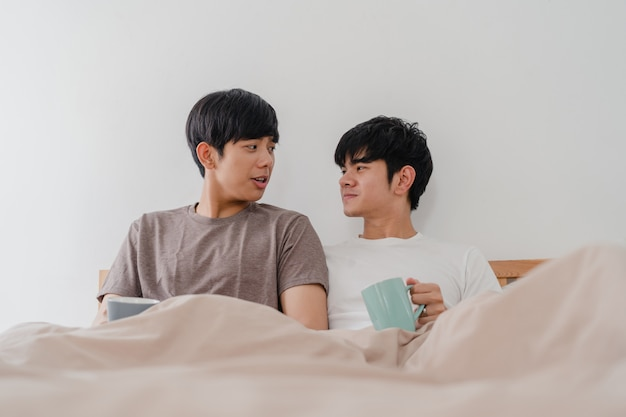 Coppie asiatiche degli omosessuali che parlano divertendosi a casa moderna. il giovane maschio dell'amante dell'asia felice si rilassa il caffè della bevanda di resto dopo si sveglia mentre si trova sul letto in camera da letto a casa di mattina.