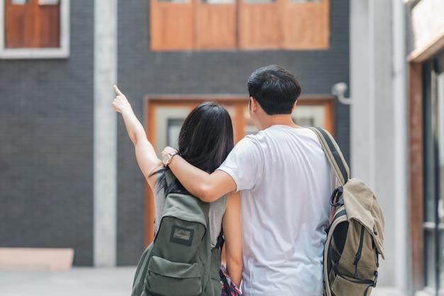Coppie asiatiche del viaggiatore con zaino e sacco a pelo del viaggiatore che ritengono viaggio felice a pechino, cina, coppie allegre del giovane adolescente che camminano a chinatown.
