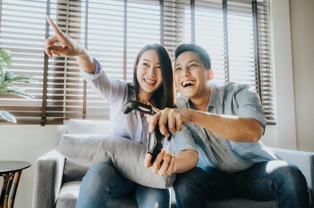 Coppie asiatiche emozionanti divertendosi giocando video gioco a casa