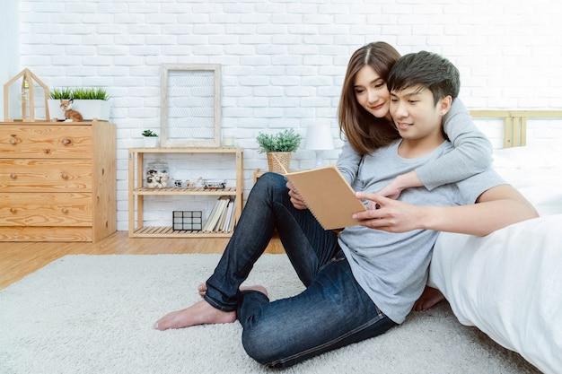 Coppie asiatiche felici che leggono il libro o il taccuino sul letto nella camera da letto a casa moderna, amante e