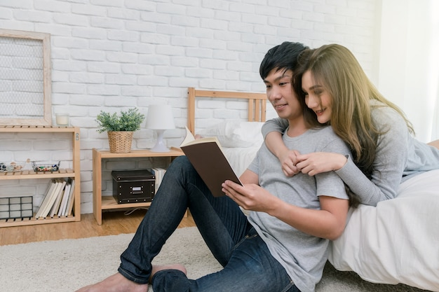 Coppie asiatiche felici che leggono il libro o il taccuino sul letto