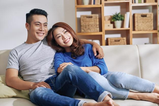 Coppie asiatiche felici che si siedono insieme sullo strato a casa, distogliendo lo sguardo e sorridendo