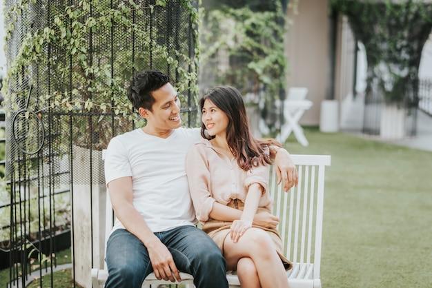 Coppie asiatiche felici che sorridono mentre sedendosi sul banco