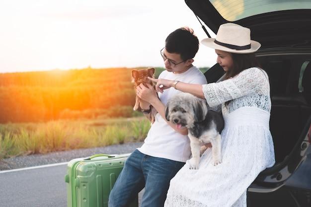 Coppie asiatiche felici e giovani che godono dello stile di vita di viaggio di vita con gli animali domestici.