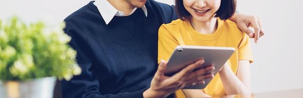 Coppie asiatiche felici facendo uso della compressa digitale e online insieme a casa