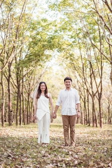Coppie asiatiche felici nell'amore con l'arco dell'albero