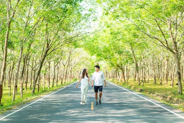 Coppie asiatiche felici nell'amore sulla strada con l'arco dell'albero