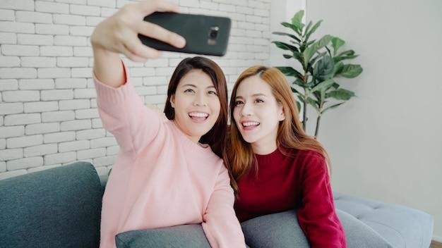 Coppie asiatiche lesbiche che utilizzano selfie dello smartphone in salone a casa