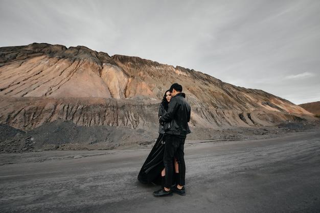 Coppie asiatiche nell'amore in vestiti di cuoio neri che camminano in natura. stile, moda, amore