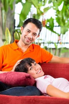 Coppie asiatiche nella casa spaziosa sul sofà
