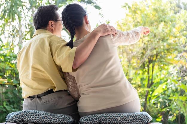 Coppie asiatiche senior che abbracciano e che si siedono sul sofà in salone a casa.