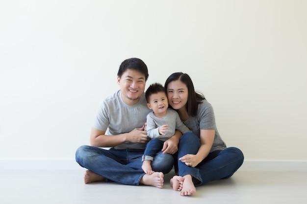 Coppie asiatiche sorridenti e figlio che si siedono sul pavimento nel concetto nucleo familiare tailandese e cinese felice di discesa della stanza
