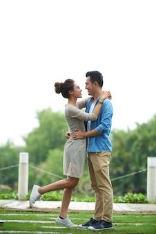 Coppie asiatiche spensierate che abbracciano alla data