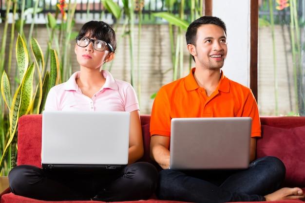 Coppie asiatiche sul divano con un computer portatile