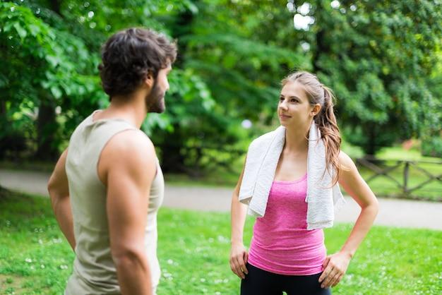 Coppie atletiche che parlano in un parco
