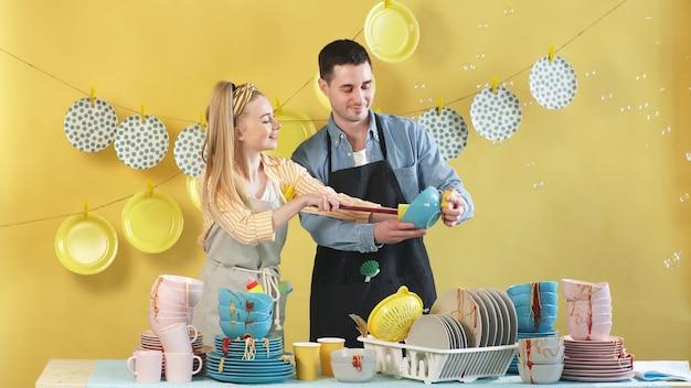 Coppie attraenti che fanno insieme le faccende domestiche, lavando i piatti, fondo isolato