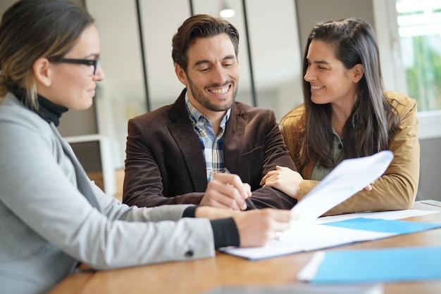 Coppie attraenti che firmano accordo di vendite con l'agente immobiliare