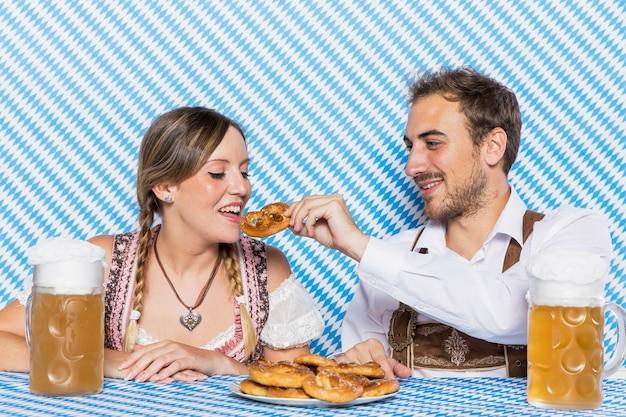 Coppie bavaresi che assaggiano ciambellina salata tedesca