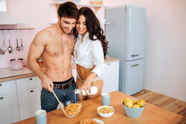 Coppie calde felici insieme in cucina. giovane uomo si sfalda con il cucchiaio. la donna versa il latte nella ciotola. si abbracciano e sorridono.