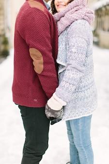 Coppie caucasiche felici e romantiche in maglioni caldi che camminano nella città leopoli di inverno. vacanze, inverno, amore, bevande calde, persone